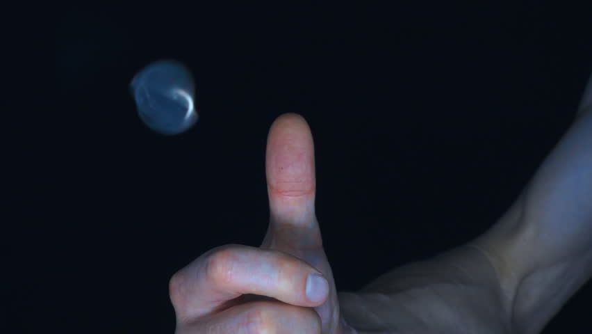 The thumb of the hand strikes a metal coin and it spins up into the air and falls on a black background. Closeup. Slow mo, slo mo, slow motion, high speed camera, 240fps, 250fps