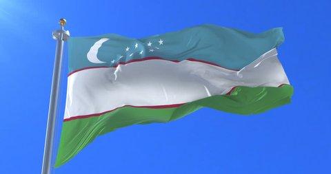 Uzbekistan flag waving at wind in slow with blue sky, loop