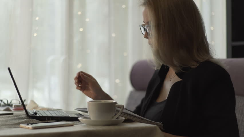 Business woman in glasses typing on keyboard notebook sitting at couch in cafe with coffee cup. Beautiful woman working on wireless laptop during business lunch in modern cafe | Shutterstock HD Video #33985771