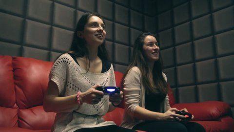 Two young girls playing video games with game controller on red sofa