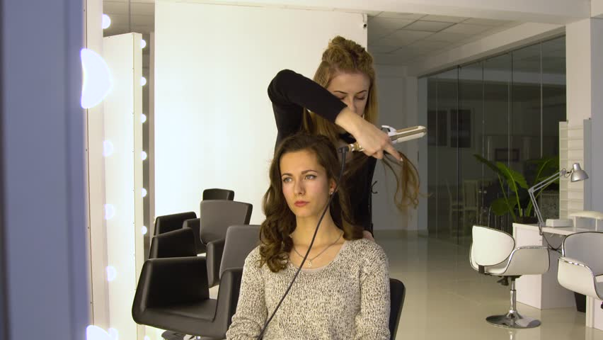 Young beautiful girl in beauty salon. Hairdresser-stylist makes the girl's hair. The hairdresser curls the hair with a styler and stacks them. | Shutterstock HD Video #34004395