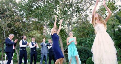 Bride throwing wedding bouquet to wedding guest at wedding 4K 4k