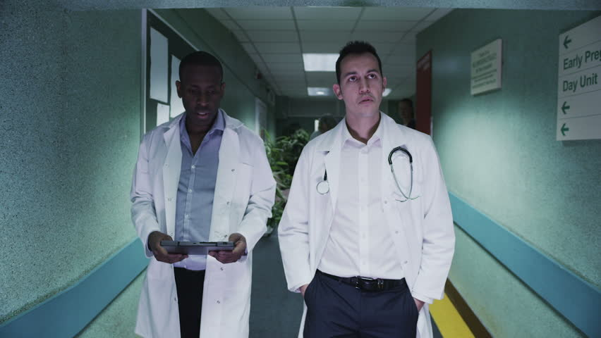 Two male doctors discuss a patient's notes as they walk down a hospital corridor. Other medical staff and patients can be seen in the background.