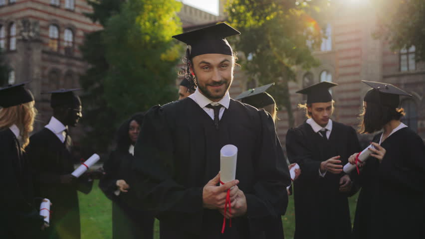 Portrait of the handsome man graduate standing in traditional graduation clothes with diploma in hands and looking to the sky with a hope. Graduates on the background. Outside