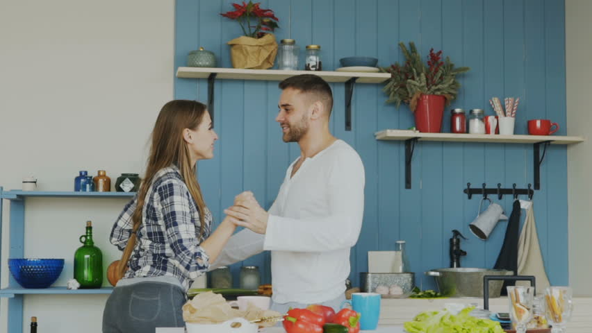 Slowmotion of Cheerful and attractive young couple in love dancing together latin dance in the kitchen at home on holidays #34071565