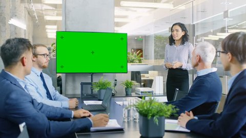 Beautiful Businesswoman Gives Report/ Presentation to Her Business Colleagues in the Conference Room, She Interacts with Wall TV with Green Chroma Key Screen. Shot on RED EPIC-W 8K Helium  Camera.