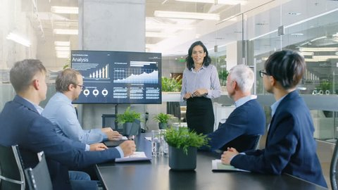 Chief Female Executive Gives a Report/ Presentation to Her Colleagues in the Meeting Room, She Shows Graphics, Pie Charts and Company's Growth on the Wall TV.