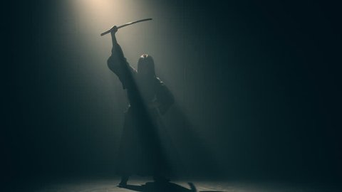 Martial arts Concept. Woman in kimono practicing with katana