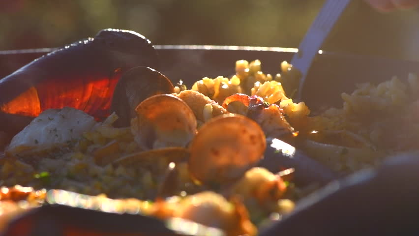 Seafood Paella cooking. Traditional Spanish paella with prawns, mussels and fish. Person cooking fresh delicious paella closeup. 4K UHD slow motion video
