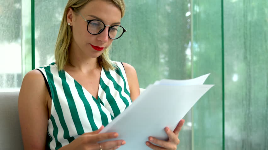 Creative young woman in stylish eyewear carefully learning summary text material written on pages of paper documentation for improve design skills resting on comfortable sofa in modern apartment