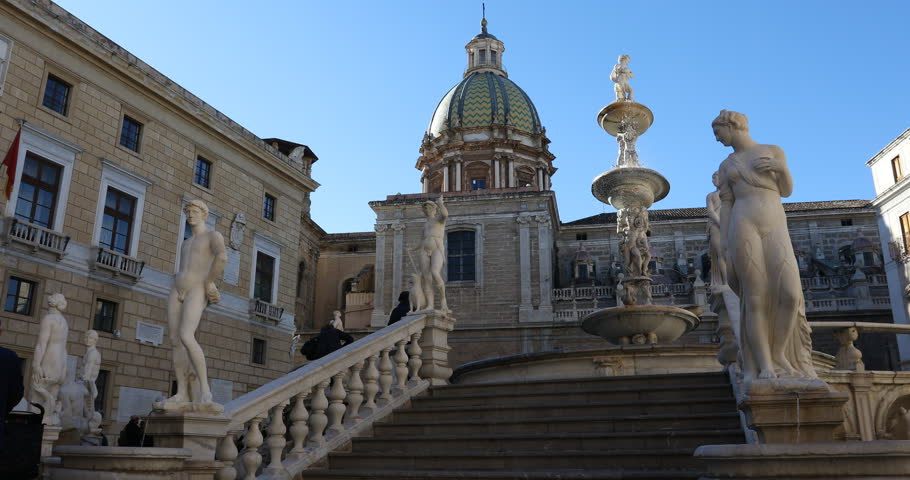 Palermo, Sicily, Italy. Dec 08 2017: fountain with detailed statues of white marble, called Pretoria Fountain, and church dome at background . Ita: Fontana Pretoria (Fontana della Vergogna).