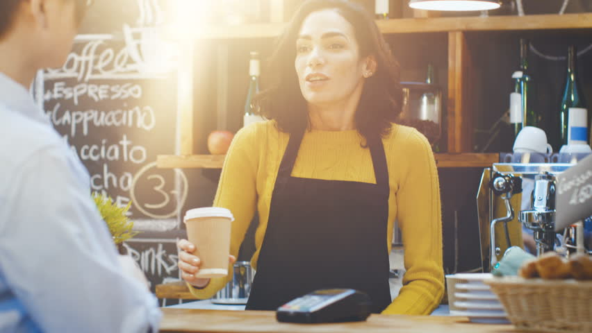 In the Cafe Beautiful Hispanic Woman Makes Takeaway Coffee For a Customer Who Pays by Contactless Mobile Phone to Credit Card System.  | Shutterstock HD Video #34161175