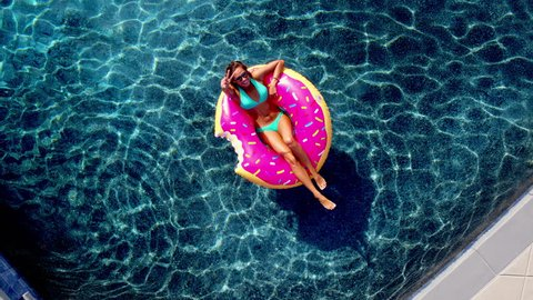 Young happy woman relaxing on inflatable pool toy in blue swimming pool on sunny day waiving at camera