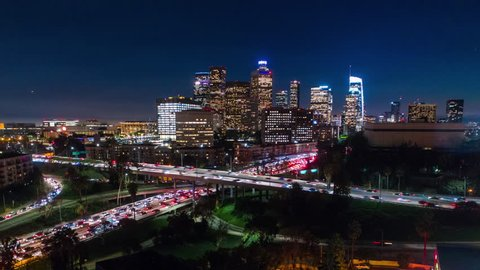 Cinematic urban aerial hyper lapse of downtown Los Angeles freeways with heavy traffic, city skyline and sky scrapers at night.
