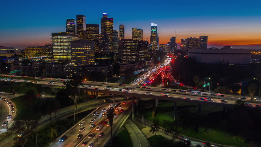 Cinematic urban aerial hyperlapse of downtown Los Angeles freeways and traffic with city skyline and skyscrapers at sunset with deep blue and orange colors.