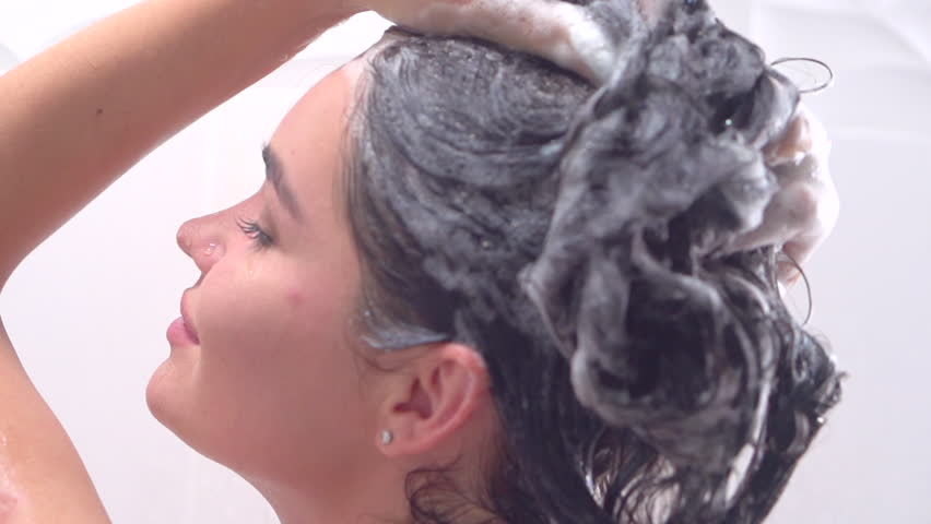 Woman Washing Hair. Young beautiful girl taking a shower and gently touching her skin, washing head with shampoo. Slow motion 4K video footage. Ultra high definition 3840X2160