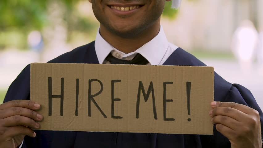 Graduate of prestigious university holding sign with inscription hire me, career
