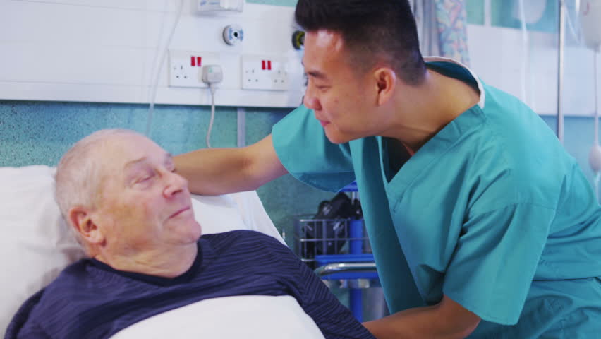 A male nurse attends to an elderly male patient, holding his hand and chatting with him. In slow motion.