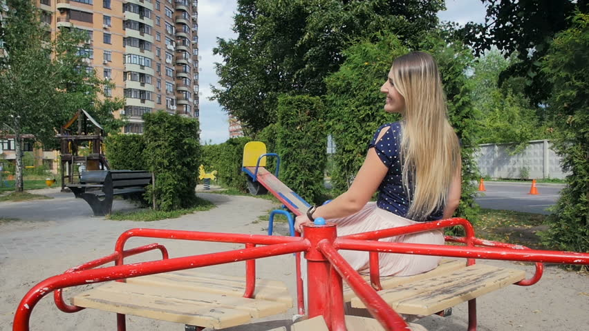 Slow motion video of beautiful young woman riding on carousel at playground | Shutterstock HD Video #34255135
