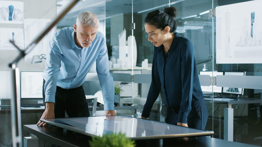 Senior Male and Young Female Architectural Designers Draw Building Concept on a Graphics Tablet Display Vertical Touchscreen Table. They Use Gestures for Zooming Project Model. 4K UHD.