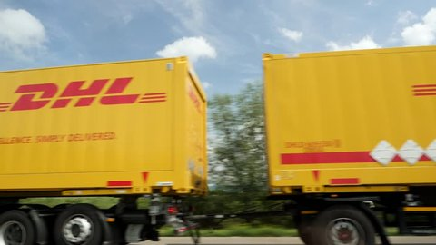 Bremen, Germany - Circa 2017: Busy German autobahn with DHL delivery truck transporting letters and parcels driving slow motion on warm summer day in Nord Germany