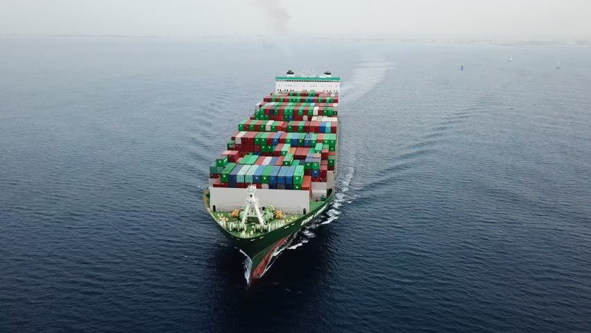 Aerial footage of a Mega Container ship sailing across The Mediterranean sea