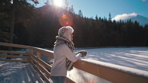 Slender Young Lady is Admiring the Mountain Lake under snow in Winter with Amazing Sun Lense Flare