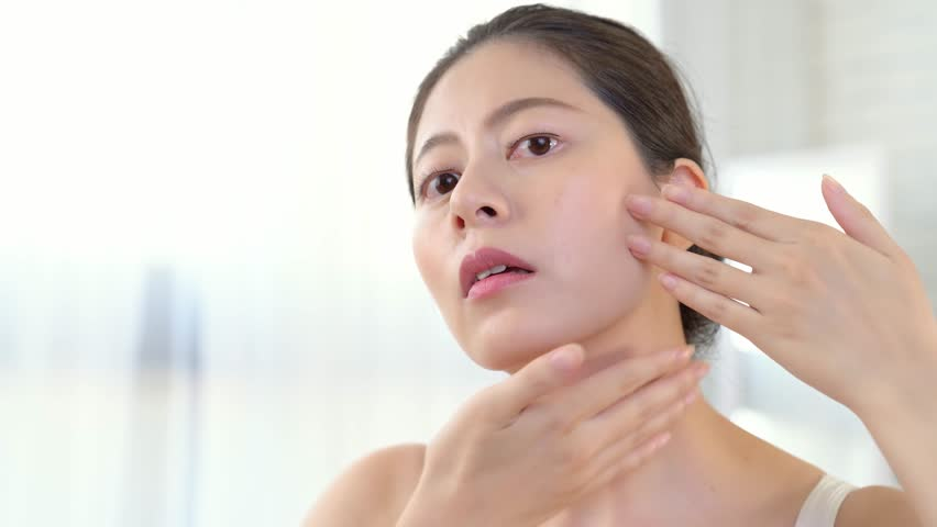 beautiful asian girl model applying cosmetic cream treatment on her face on bedroom background