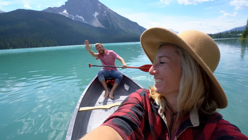 Young couple canoeing on a beautiful lake in Canada, taking selfies. Selfie portrait of couple canoeing on Emerald lake, Canada | Shutterstock HD Video #34286425