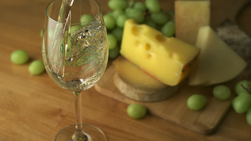 Pouring white wine into glass with grape and cheese shooting with a high speed camera.