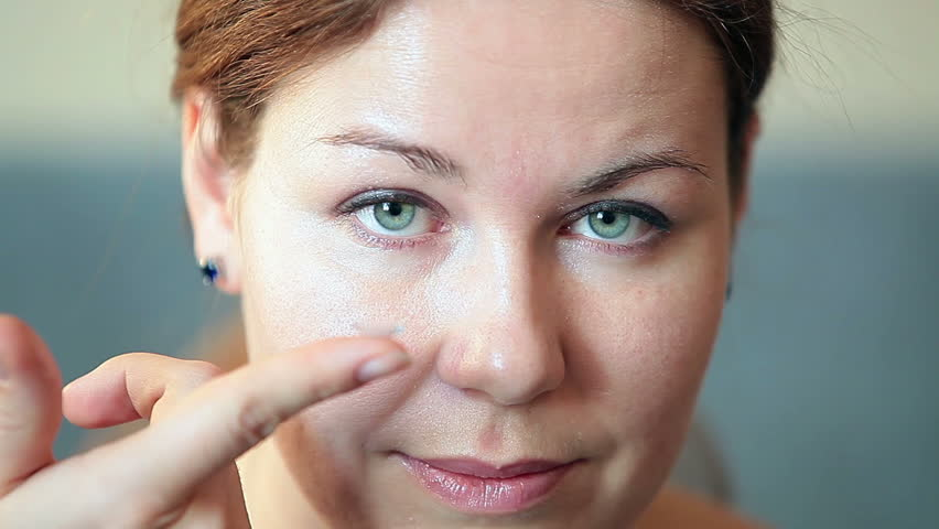 Young woman holding clear transparent contact lens on finger. Short video