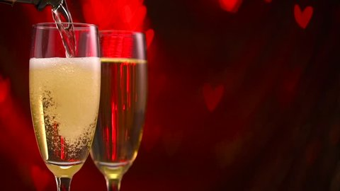Pouring Champagne in two glasses over holiday blinking red background with hearts. Valentine's Day, Wedding celebrating. Couple of flute with champagne close up. Slow motion 4K UHD video