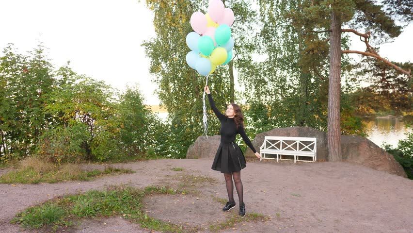 Cheerful young brunette woman turn around in high spirits, hold light flying balloons in hand. Calm corner at nice park, adorable girl in black dress feel good and happy like child