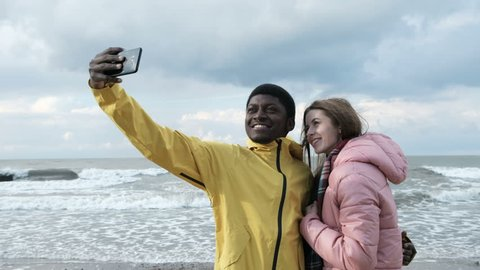 Two multicultural persons of black guy and caucasian female make a photography at smart phone close up. Positive fun concept of relations at windy spring vacation, cellphone take a pic with seaside