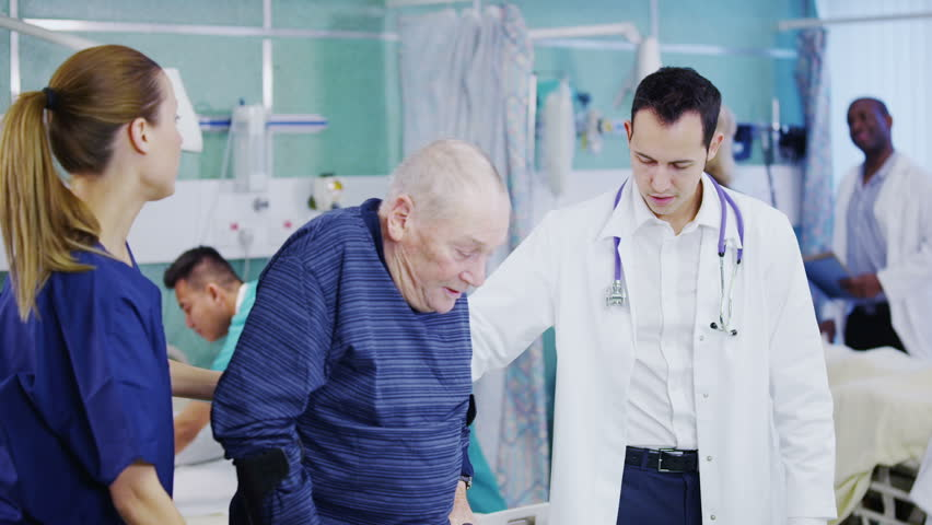 An attractive and caring young doctor and nurse help an elderly male patient to walk. Other doctors and nurses can be seen attending to other jobs in the background. In slow motion.