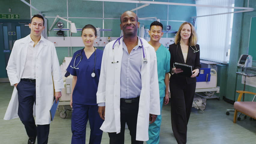 Attractive group of medical personnel of mixed ages and ethnicity stand and pose for a group portrait. | Shutterstock HD Video #3432446