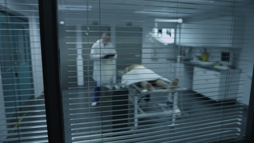 The lifeless naked corpse of a young mixed race male is laid out on the autopsy table, being inspected the medical examiner. As viewed through the window.