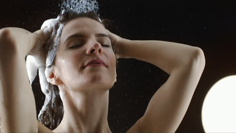 Beautiful woman head showering shampoo rinse in slow Motion. head of a  woman close up rinsing out shampoo under shower on black  background