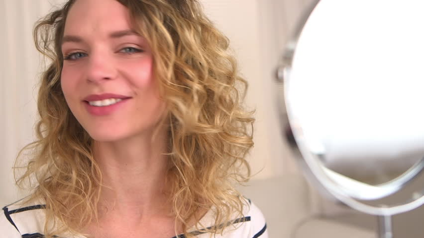 Caucasian woman shakes her hair and smiles