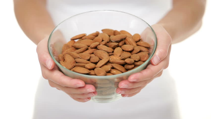 Almonds nuts - woman showing raw almond bowl closeup. Healthy food concept in studio with hands lifting bowl of unprocessed almonds up to focus on white background.