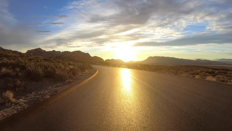 Red Rock Canyon scenic loop road rear view dawn driving in the Mojave desert near Las Vegas, Nevada.