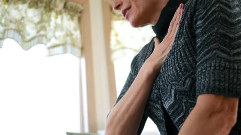 Woman rubbing her sore chest after heart condition