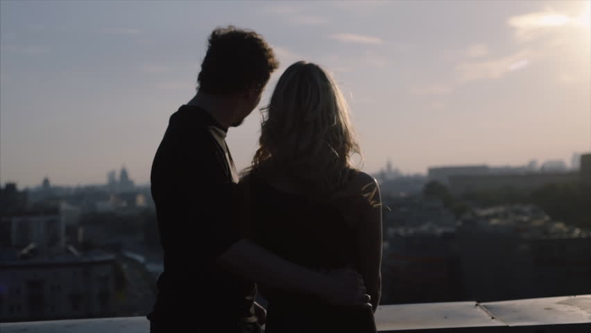 couple in rock-n-roll style standing on the roof with flapping hairs on the wind at blured citiscape background