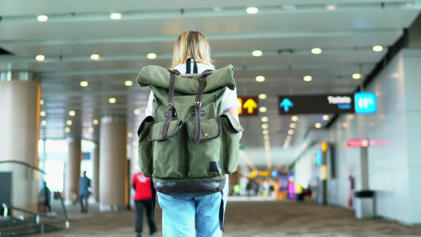 Rear view of female tourist carrying rucksack with copy space area for brand name or logo walking to gate in airport terminal