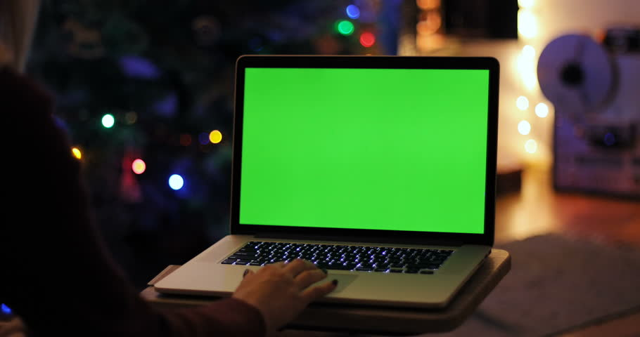 Closeup top view woman using digital modern laptop green screen chroma key free content text application clicking cosiness relaxing Christmas tree New Year holiday social networking home interior