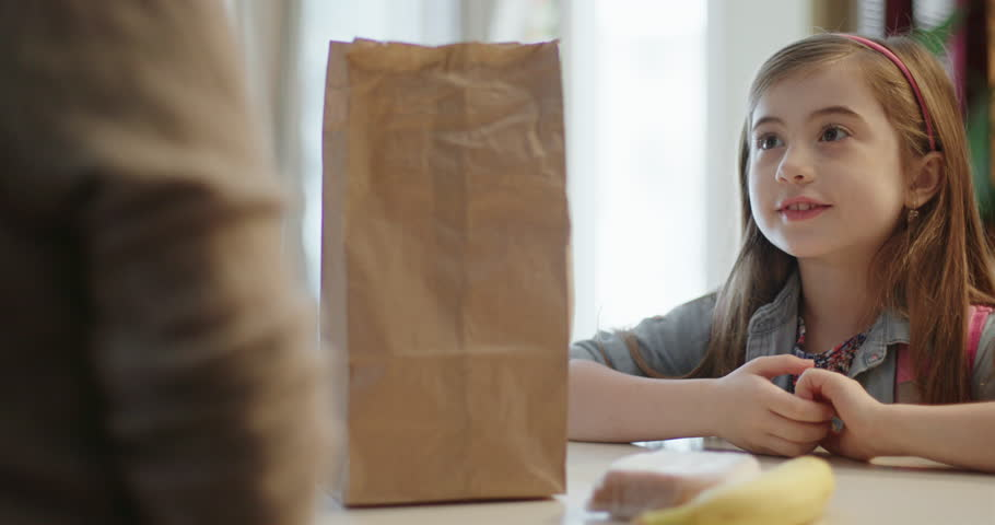 Mother Packs Lunch for Daughter. a countertop view of a mother placing a sandwich in a bag and handing the lunch bag to her daughter. She says Thank You and exits