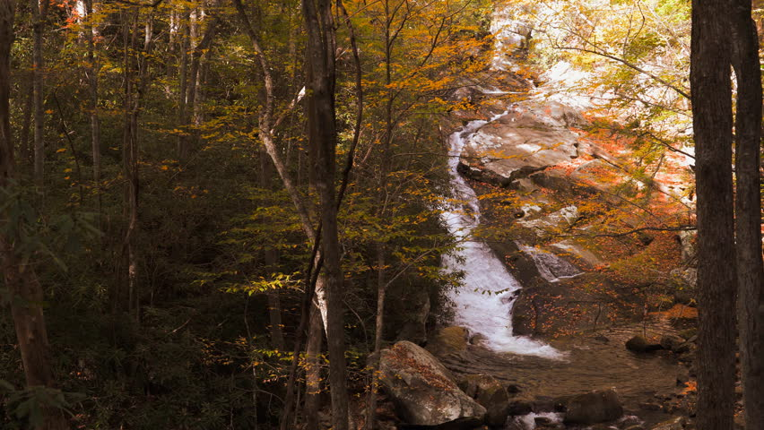 Waterfall cascades over rocks in the Appalachian mountains of Tennessee during autumn