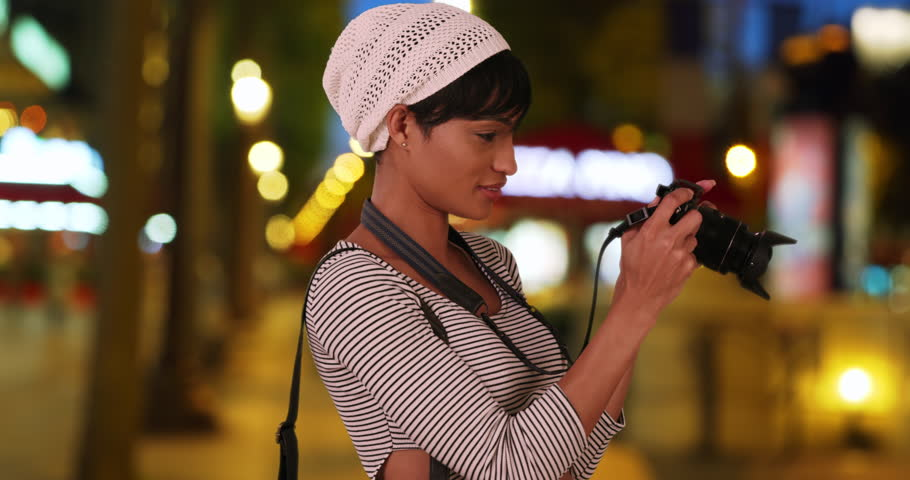 Hip African millennial girl out taking photos at night turns to the camera. Beautiful African-American artist points her camera to the viewer and takes a picture. 4k   Shutterstock HD Video #34513795