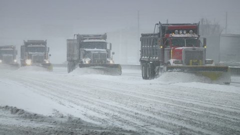 Snow Plows clearing a highway during a blizzard