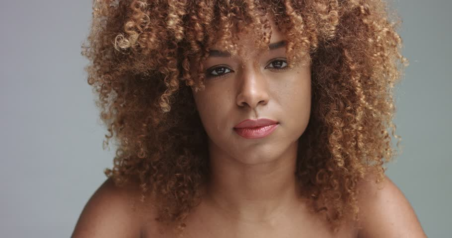 Mixed race black woman with neutral makeup portrait. Curly hair ideal skin, studio, grey background | Shutterstock HD Video #34573615